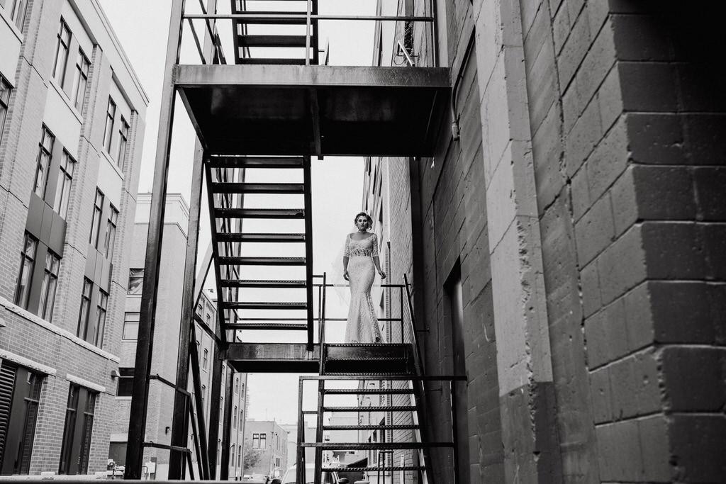 Calgary Wedding Editorial of Bride in NRT Fashions Wedding Dress on fire escape