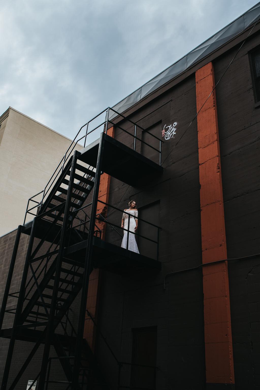 Calgary Wedding Editorial of Bride in NRT Fashions Dress on fire escape