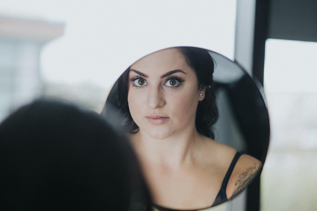Calgary Wedding Photography Bride looking in makeup mirror
