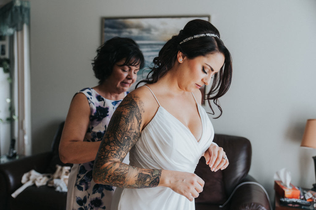 Bride's mother helping zip up dress