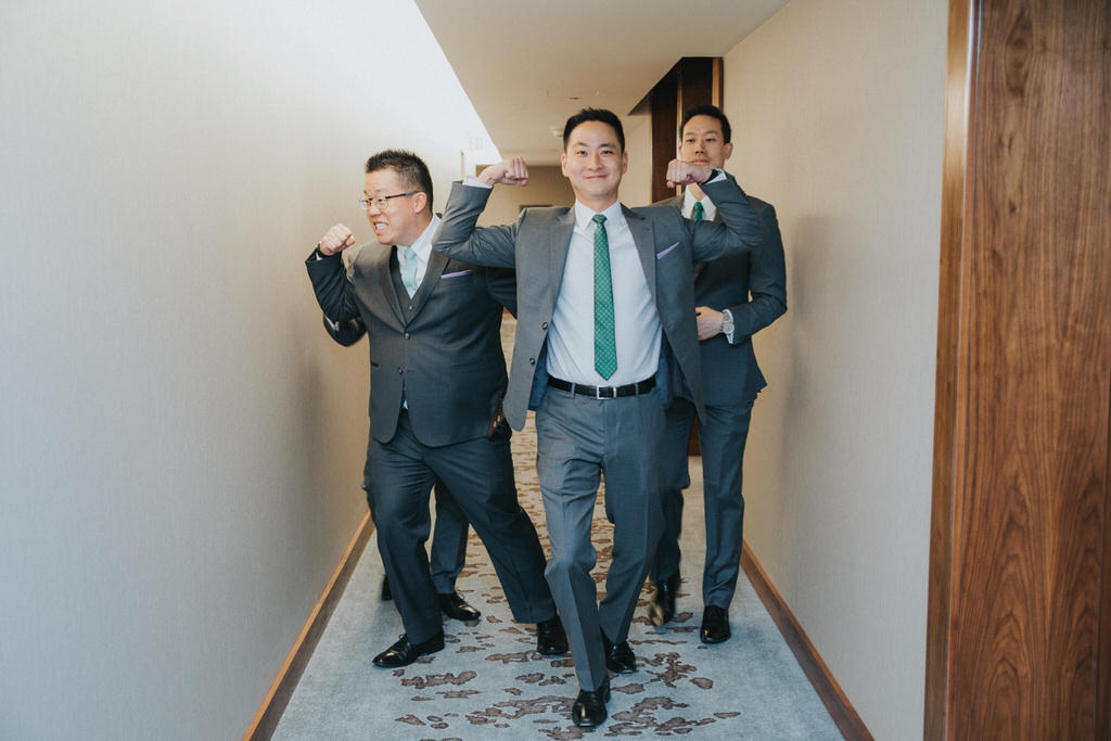Groomsmen flexing muscles in hotel hallway
