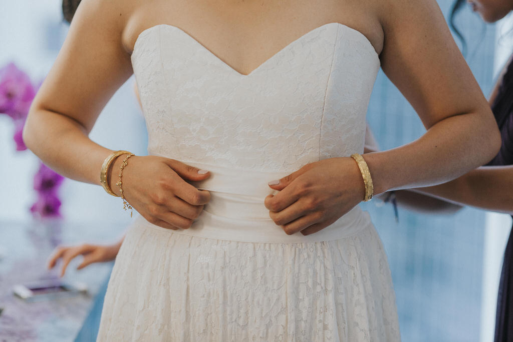 Hands adjusting wedding belt on wedding dress