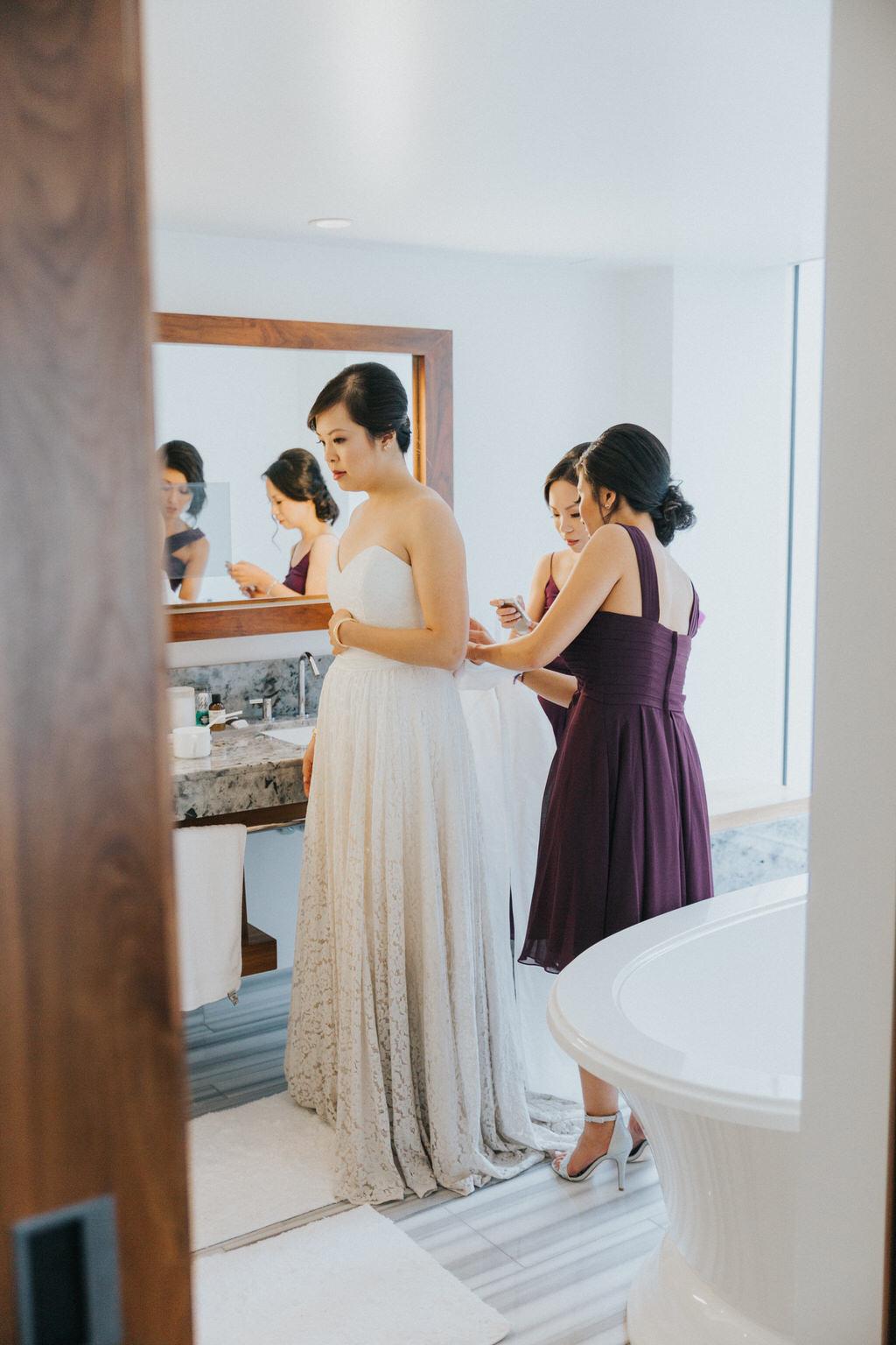 Bridesmaids zipping up brides dress