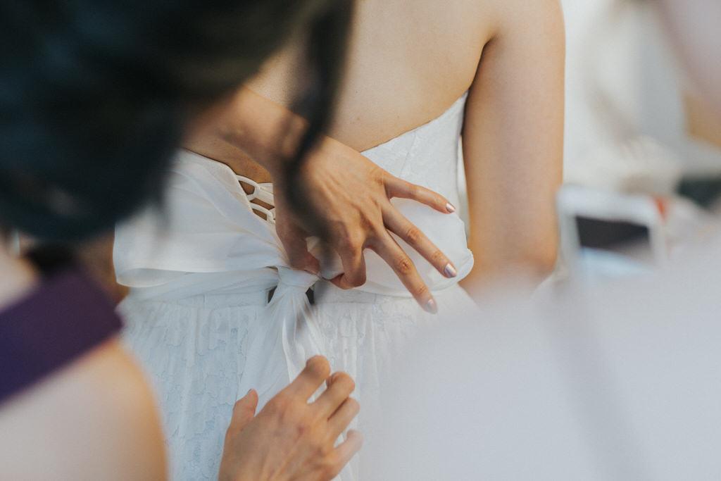 Vancouver Wedding Photography adjusting wedding dress