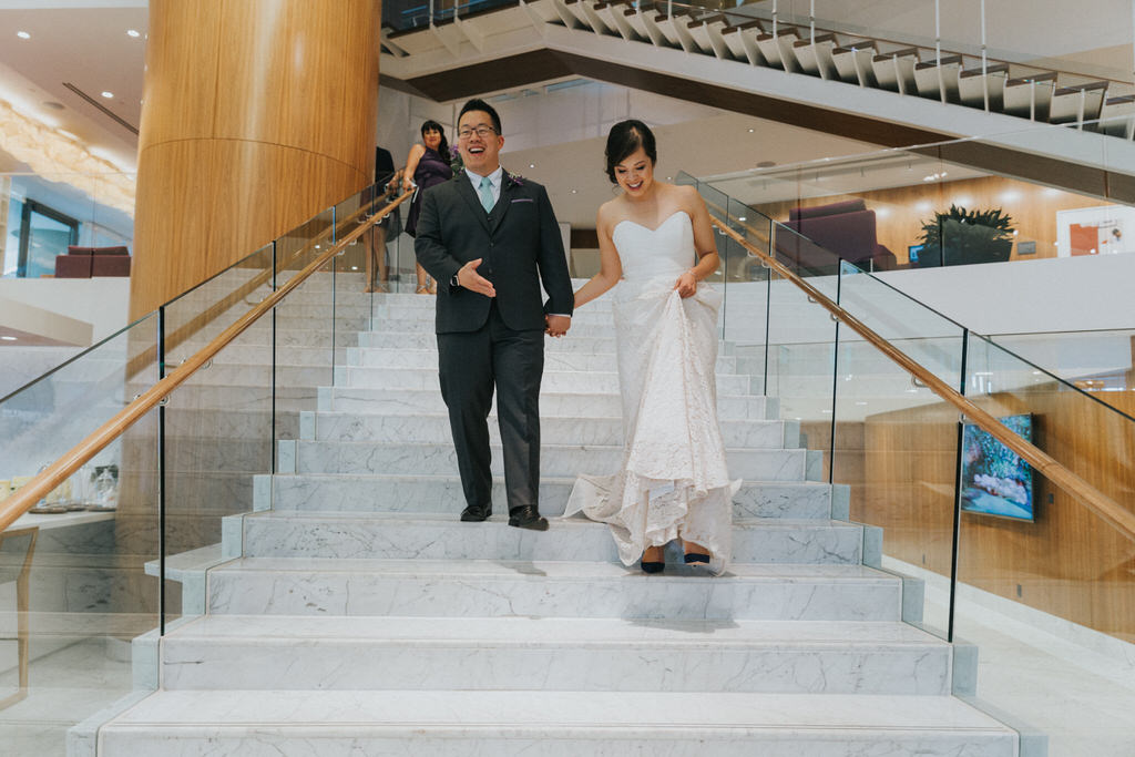 Groom and bride first look vancouver hotel walking down stairs