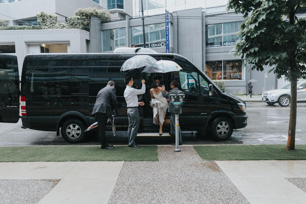 Bride getting out of wedding van to groomsmen with umbrellas