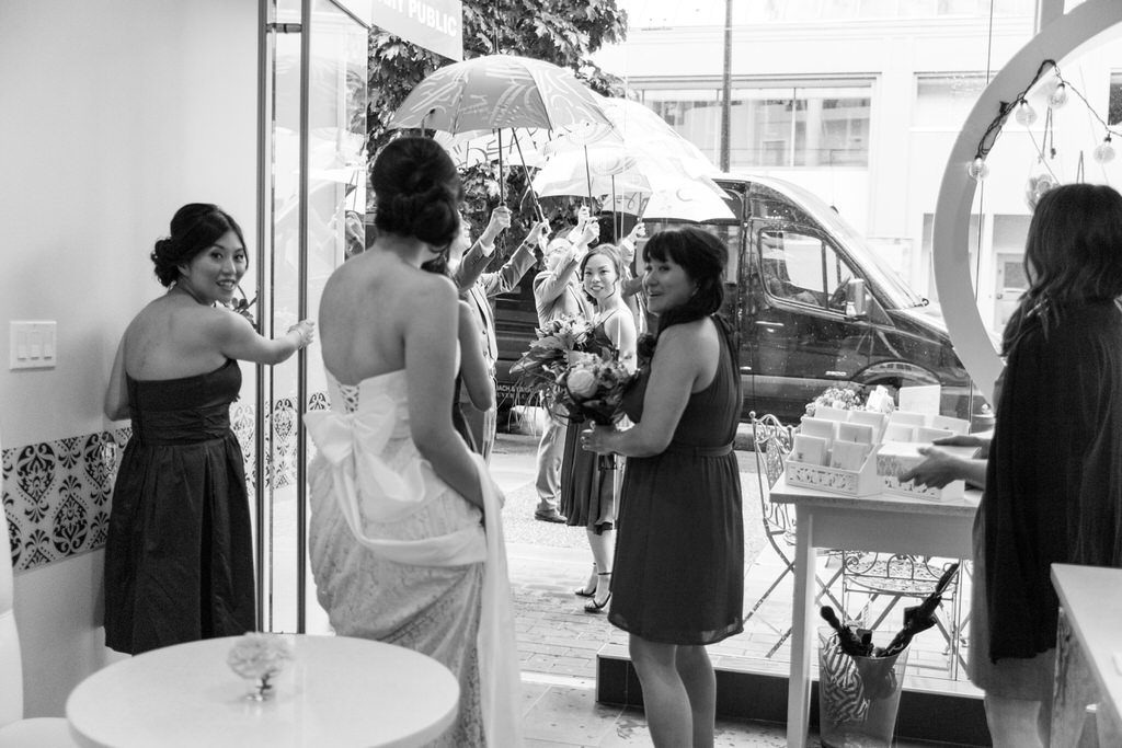 Wedding party leaving Soirette in Vancouver to awaiting umbrellas