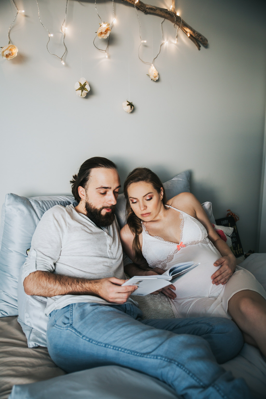 Husband With Pregnant Wife in bed reading book
