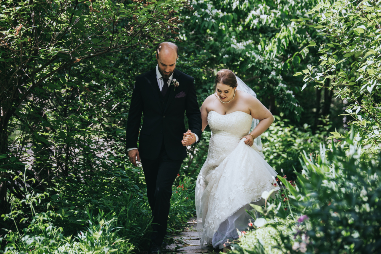 bride and groom walking through garden in calgary