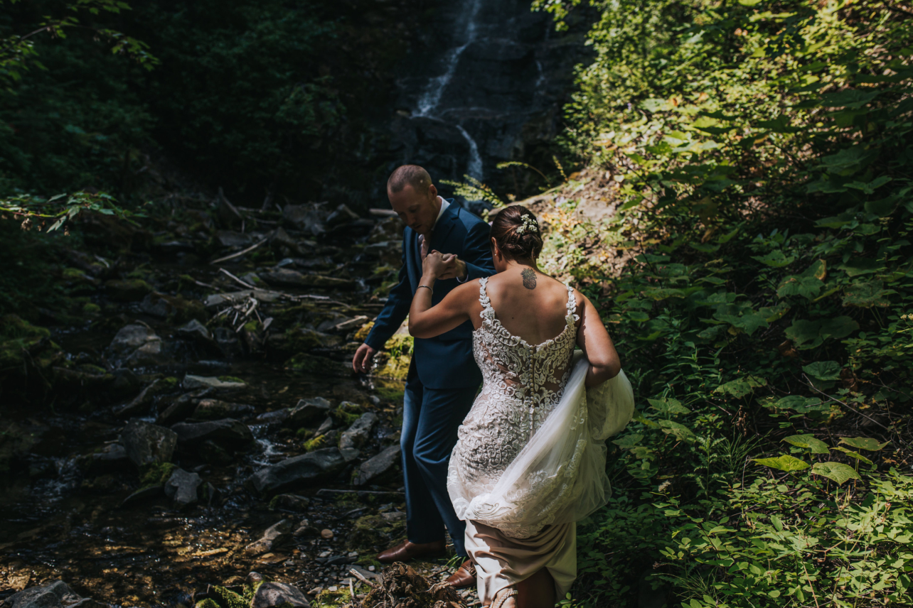 Bride and Groom walking towards waterfall